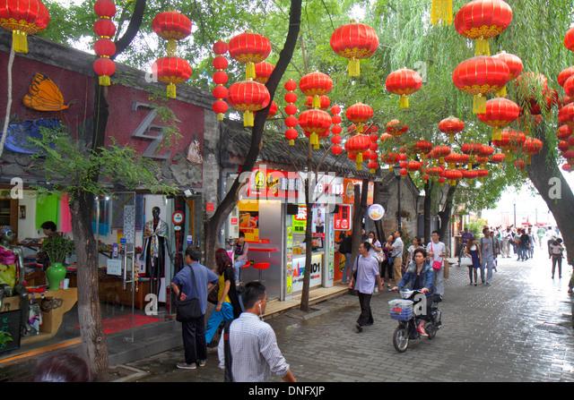 Beijing China Dongcheng District Nanluoguxiang hutong historic shopping Asian man red lanterns hanging pedestrians - Stock Image