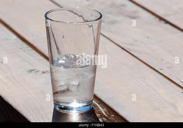 Ice water in a clear glass can either be seen as half full or as half empty. - Stock Image