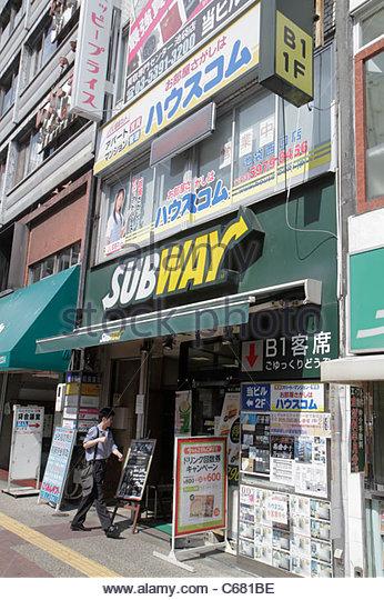 Japan Tokyo Ikebukuro business kanji hiragana katakana characters symbols Japanese English Subway Sandwich Shop - Stock Image
