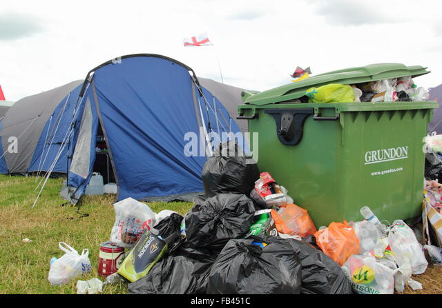 Rubbish overflows from a bin next to festival goers' tents - final day of  the Y Not festival, Pikehall, Derbyshire - Stock Image