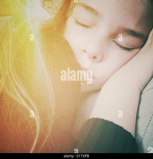 Closeup of sleeping 10 year old girl with yellow sunlight effect over shoulder - Stock Image
