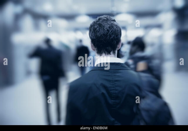 people walking in metro, blurred motion, back of the man - Stock Image
