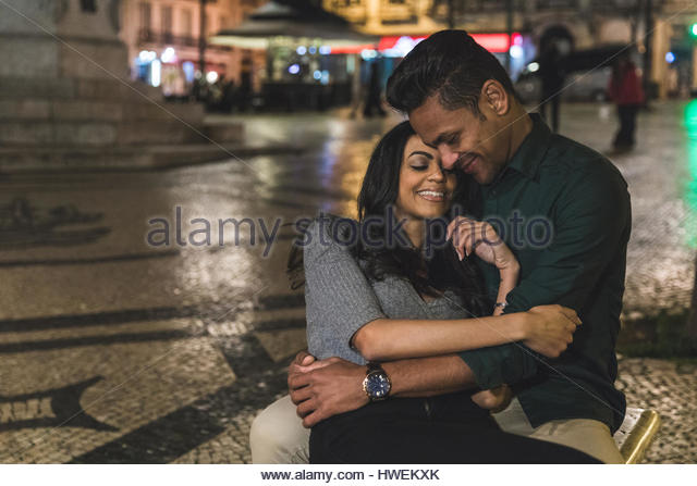 Couple in city at night, hugging, smiling, Lisbon, Portugal - Stock-Bilder