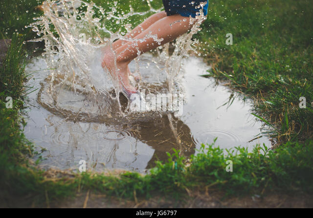 A child jumps in a mud puddle with water splashing around his feet. - Stock Image