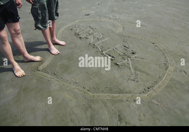 High angle view of human legs and heart on beach - Stock Image