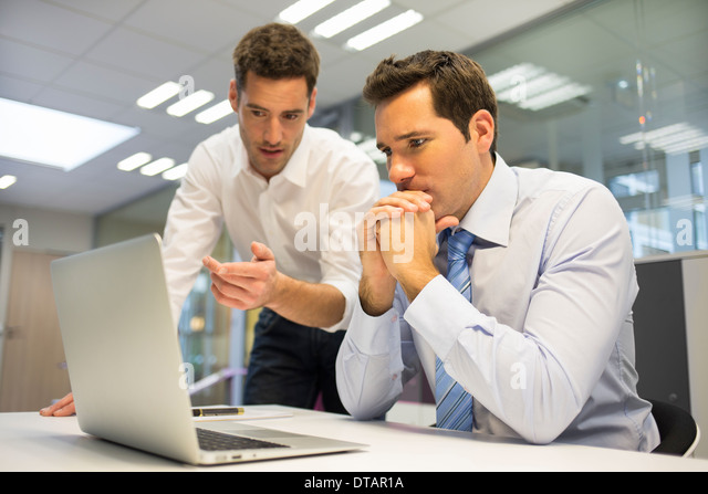 Two handsome businessmen working together on a Laptop in the office - Stock Image