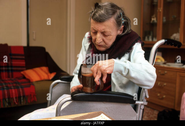 Arthritic elderly woman in wheelchair drinking coffee - Stock Image
