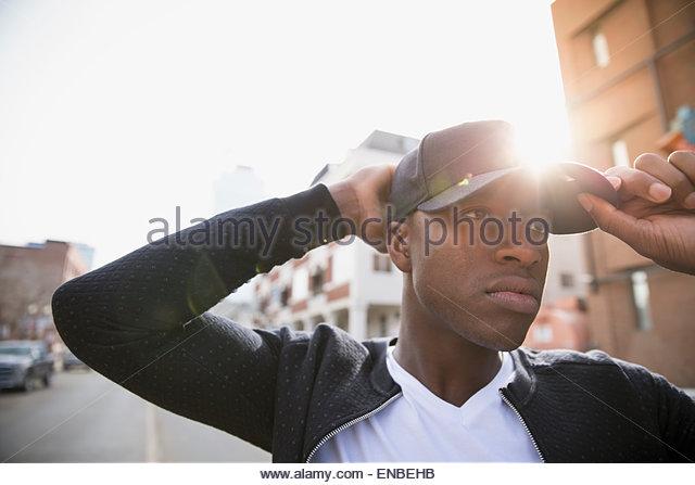 Serious man adjusting baseball cap urban street - Stock Image
