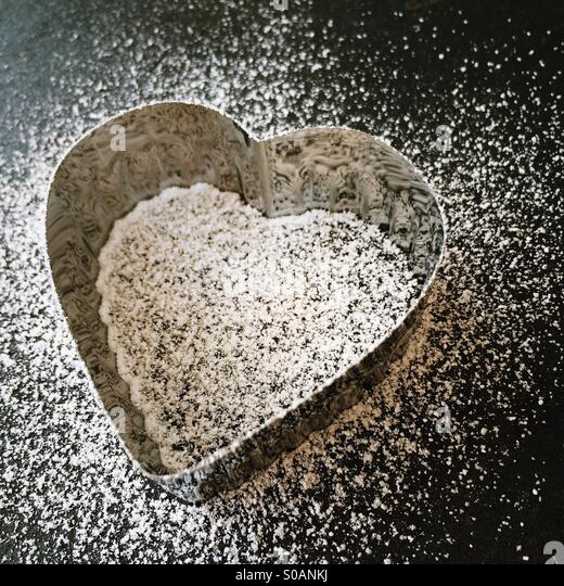 Heart shaped cookie cutter, dusting of icing sugar, black slate board, angled - Stock-Bilder