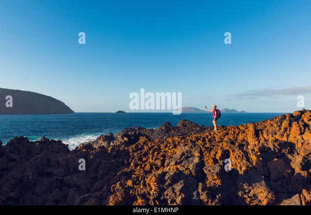 Woman hiking at La Graciosa Island, Lanzarote, Canary Islands, Lanzarote, Spain, Europe. - Stock Image