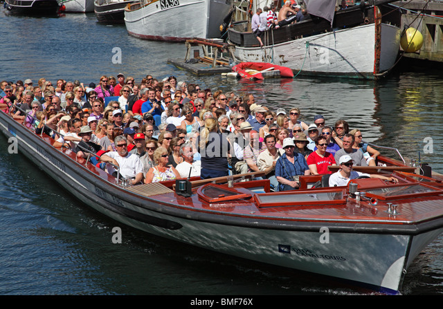 A canal tour cruise boat full of summer tourists is leaving Nyhavn on a sightseeing cruise in the port  of Copenhagen. - Stock Image