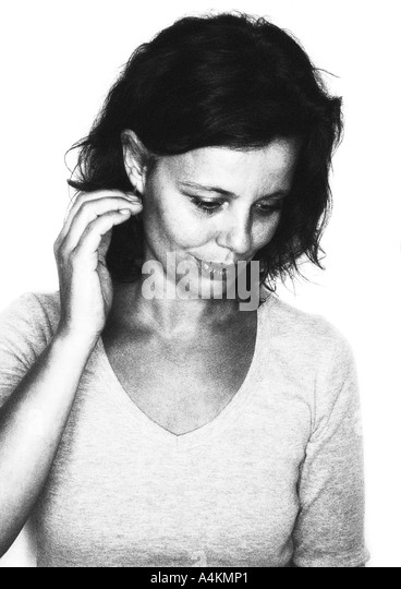 Woman looking down, smiling, portrait, b&w. - Stock Image