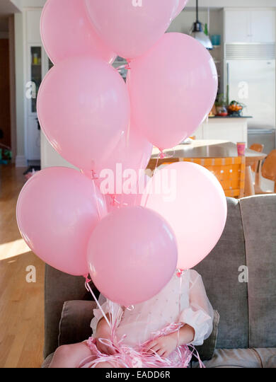 girl in pink party dress holding pink balloons - Stock Image