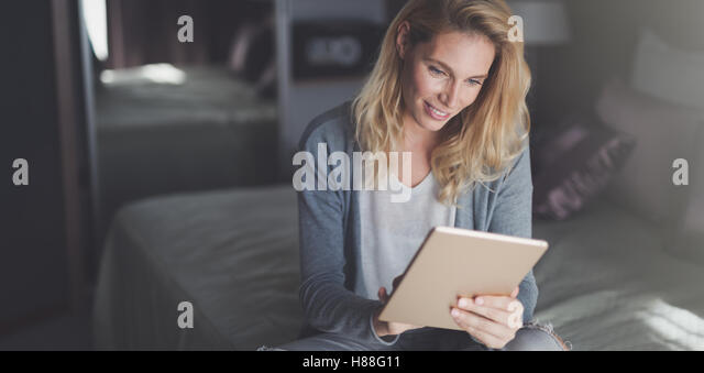 Beautiful blond woman using tablet at home - Stock Image