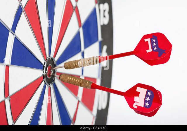 Studio shot of darts with political parties symbols in bull's-eye of dartboard - Stock Image