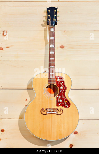 Acoustic guitar with label on a wood grain wall - Stock Image