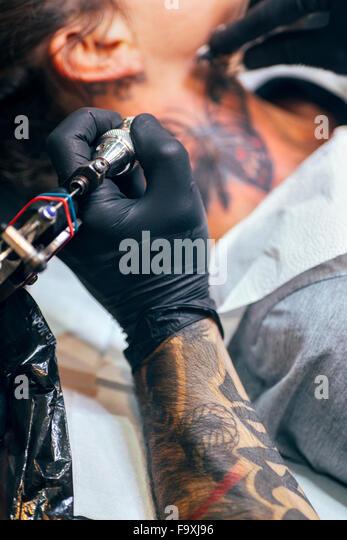 Woman receiving butterfly tattoo at her neck - Stock-Bilder