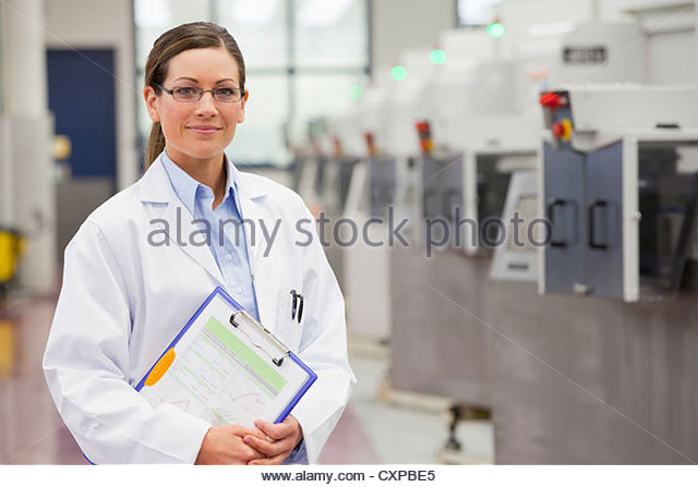 Portrait of smiling scientist holding clipboard in hi-tech manufacturing plant - Stock Image