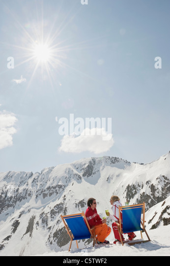 Austria, Salzburger Land, Young couple sitting in deck chair, holding glasses - Stock Image