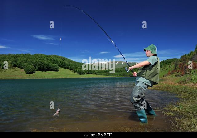 Fisherman fishing on Mavrovo lake, Macedonia - Stock Image