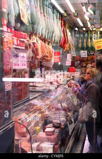 Woman chooses ham at butcher deli ham preserved meat jamon counter, Madrid, Spain - Stock Image