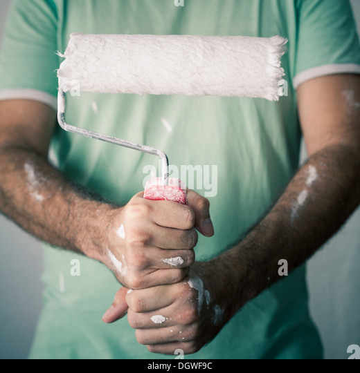 Detail of a decorator holding paint roller. - Stock Image