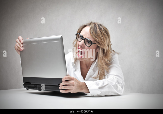 Blonde woman with glasses screaming against a laptop - Stock Image