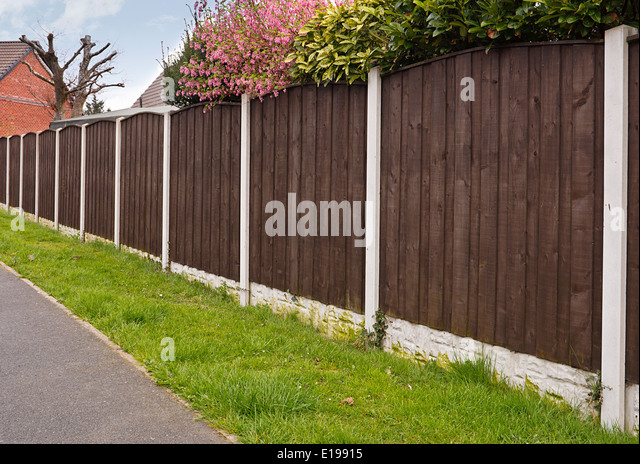close board fencing panels with concrete posts recently painted with creosote - Stock Image