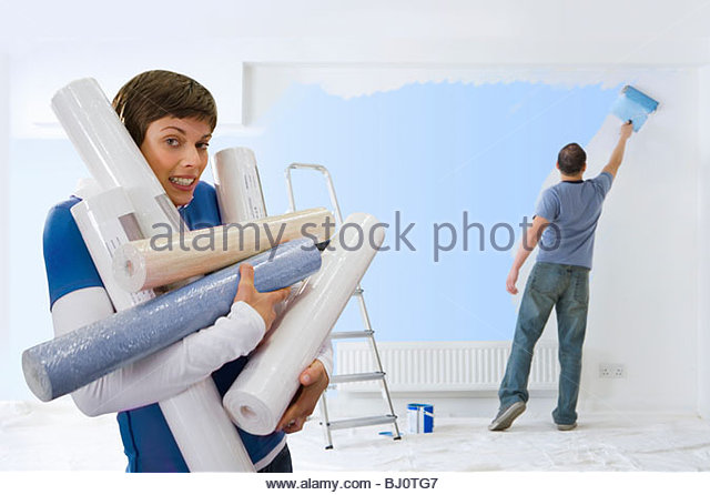 Woman carrying armful of wallpaper while husband paints - Stock Image