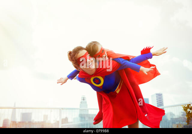 Superhero mother and daughter playing on city rooftop - Stock Image