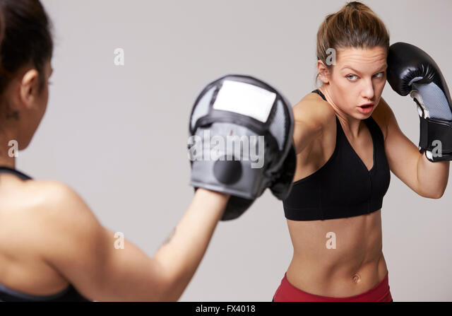 Front view of female boxer punching mitt of sparring partner - Stock Image