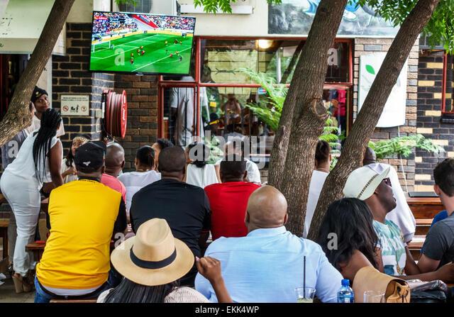 Johannesburg South Africa African Soweto Vilakazi Street Precinct Sakhumzi restaurant Black man woman watching soccer - Stock Image