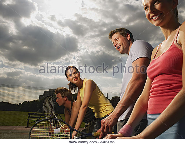 Young people on a tennis court - Stock Image