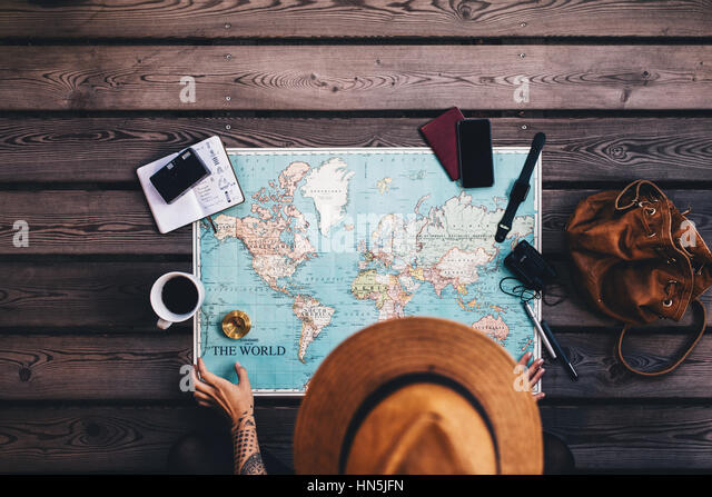 Young woman planning vacation using world map and compass along with other travel accessories. Tourist wearing brown - Stock Image