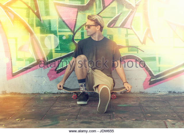 Young man sitting on skateboard, leaning against graffitied wall - Stock-Bilder