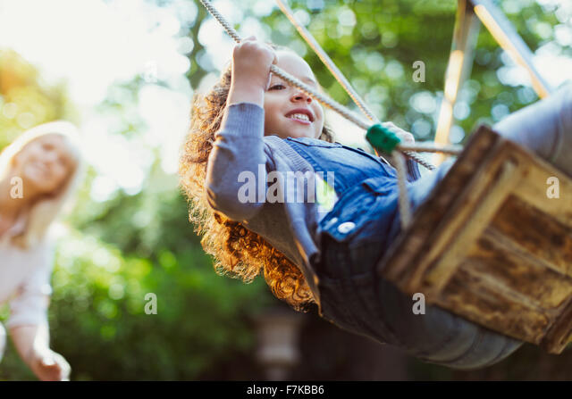 Carefree girl swinging in park - Stock Image