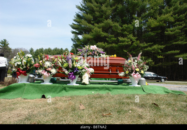 Wooden Casket and Flowers in a Cemetery Copy Space - Stock Image