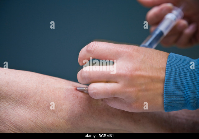 Doctor giving patient a needle - Stock Image