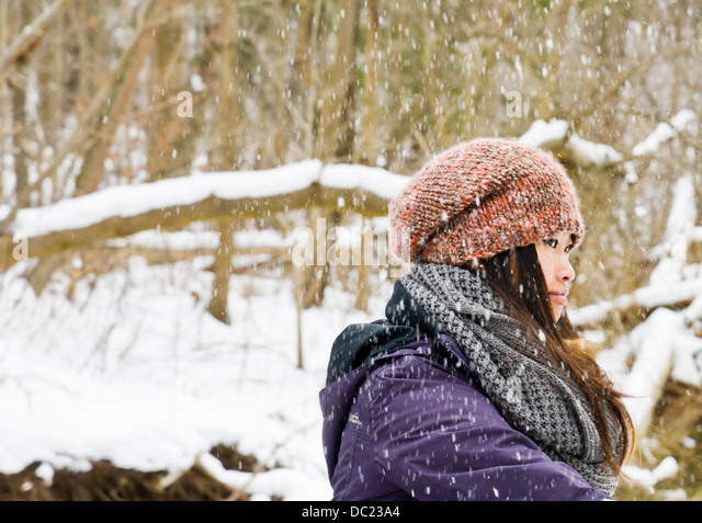 Young woman wearing knit hat and scarf in snow - Stock Image