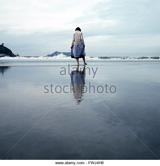Rear View Of Woman On Shore At Beach Against Sky - Stock Image