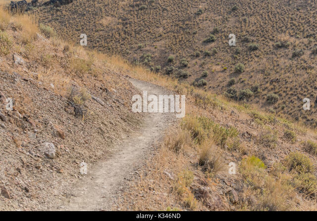 Dry Trail Bends Around Desert Hill in summer - Stock Image