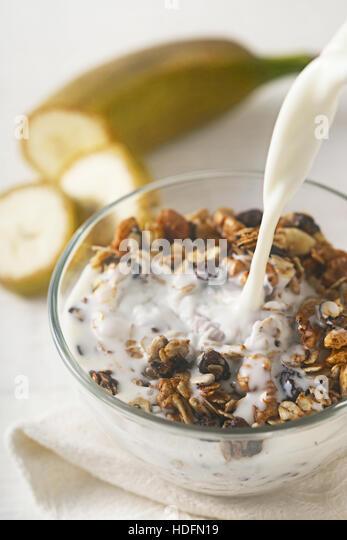 Adding yogurt to granola vertical - Stock Image