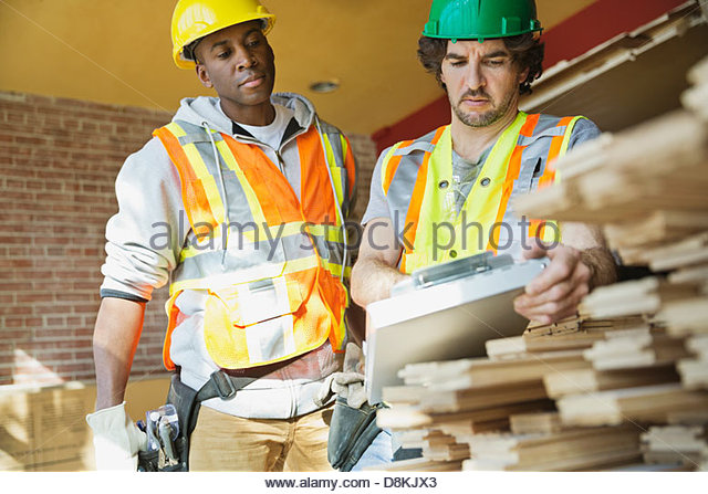 Tradesmen discussing work order at construction site - Stock Image
