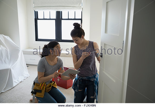Mother and teenage daughter digital tablet fixing handle - Stock Image