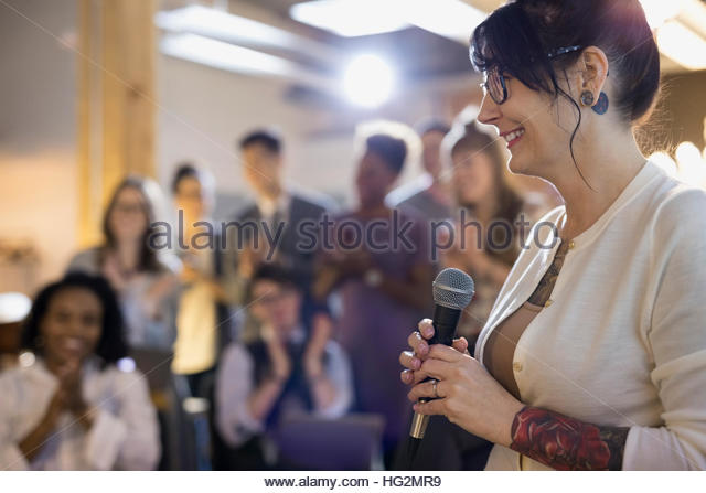 Smiling businesswoman with microphone leading conference meeting - Stock Image