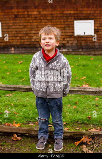 Three year old boy in a lifestyle portrait showing the child outdoors. - Stock Image