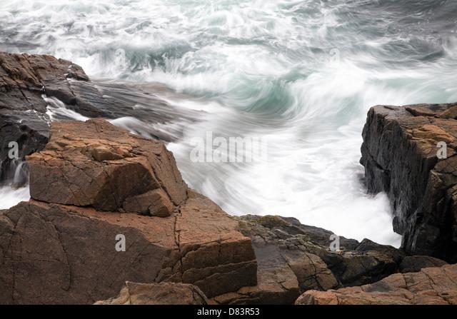 Waves crash along the rocky Maine coastline in Acadia National Park - Stock Image
