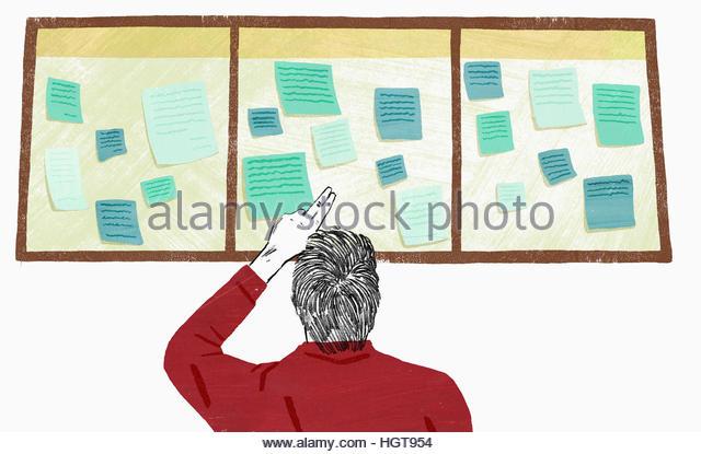 Man reading notices on notice board - Stock-Bilder