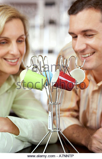 Couple looking at multi-coloured espresso cups hanging on rack in shop, close-up - Stock Image