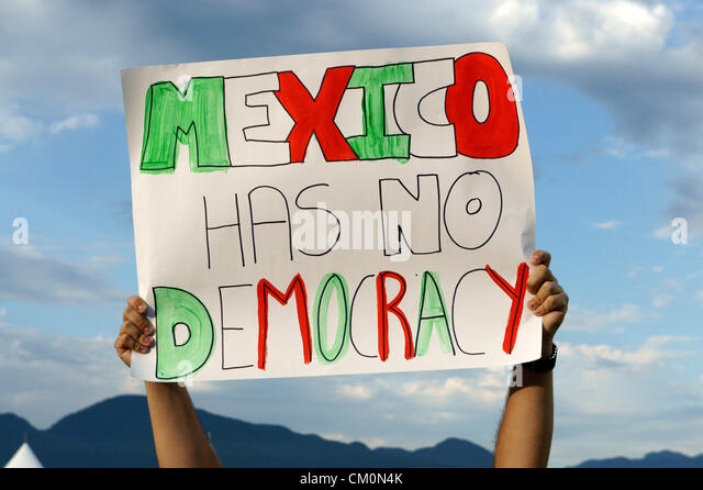Political protester holding up a sign the Mexico Fest Mexican independence day celebrationsin Vancouver, British - Stock Image